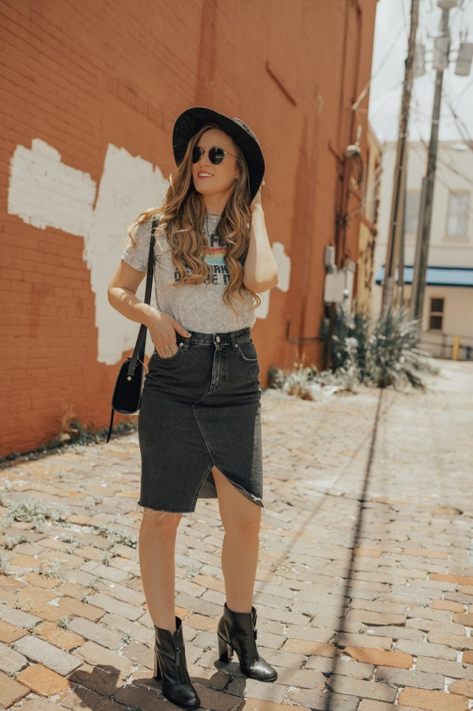 Shannon Jenkins of Upbeat Soles styles an edge concert outfit with Target band tee, H&M black denim skirt, and black zip up ankle booties