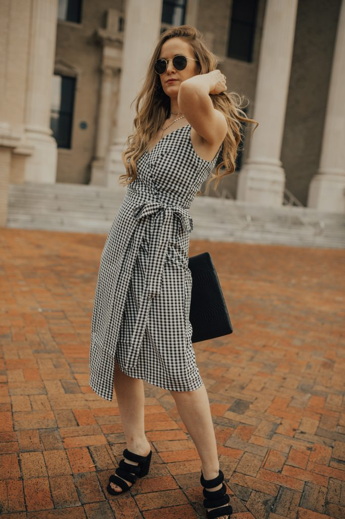 Shannon Jenkins from the fashion blog Upbeat Soles styles a gingham wrap dress from Chicwish with a GiGi New York black clutch and Kelsi Dagger black sandals