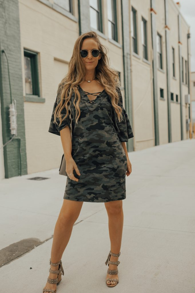Shannon Jenkins of Upbeat Soles styles a cute summer outfit with camo lace up shift dress, Dolce Vita studded sandals, and ring Rebecca Minkoff bag