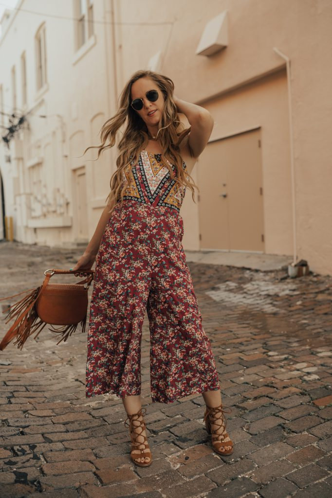 Shannon Jenkins of Upbeat Soles styles a casual jumpsuit summer outfit with patchwork Target jumpsuit, lace up heel sandals, and Sancia crossbody bag