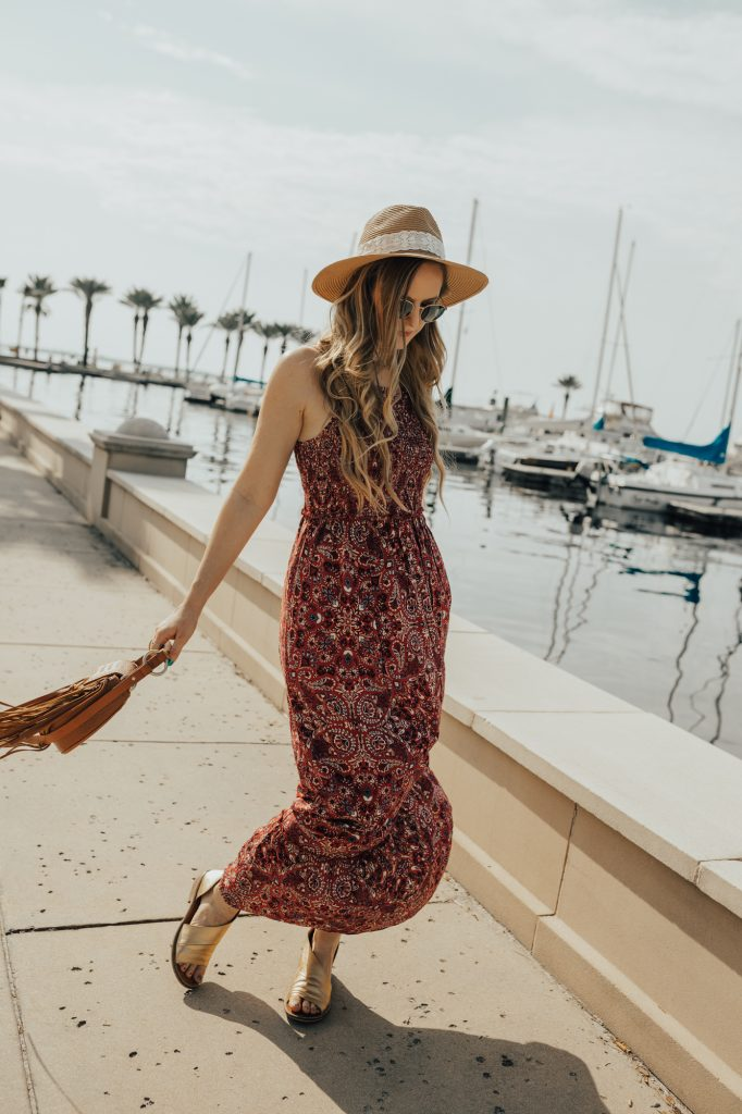 Shannon Jenkins of Upbeat Soles styles a casual summer vacation outfit with paisley Target maxi dress, Free People sandals, and Sancia crossbody bag