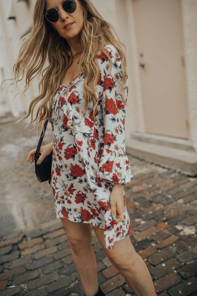 Shannon Jenkins of Upbeat Soles styles an edgy summer outfit with a floral American Eagle dress, Schutz booties, and round Ray Ban sunglasses