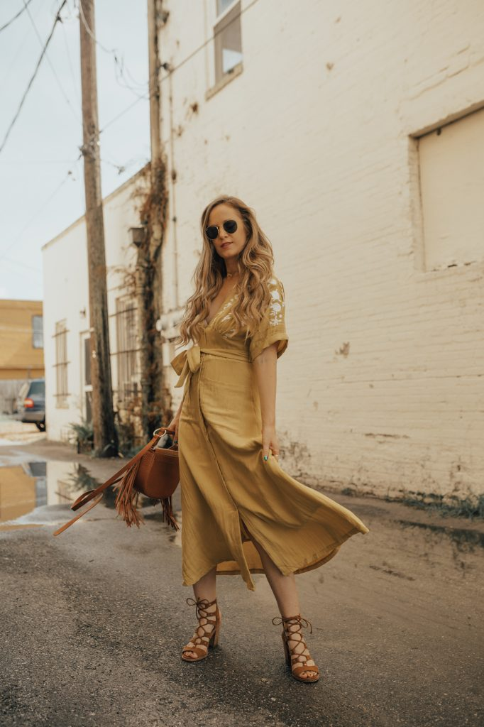 Shannon Jenkins of Upbeat Soles styles an embroidered midi dress for summer with a yellow Chicwish dress, lace up block heels, and fringe crossbody bag