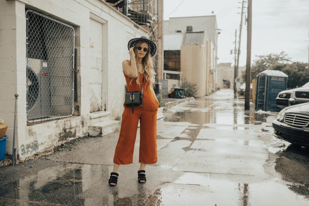 Shannon Jenkins of Upbeat Soles syles a fall transition outfit with burnt orange button jumpsuit, Kelsi Dagger sandals, and Sancia crossbody