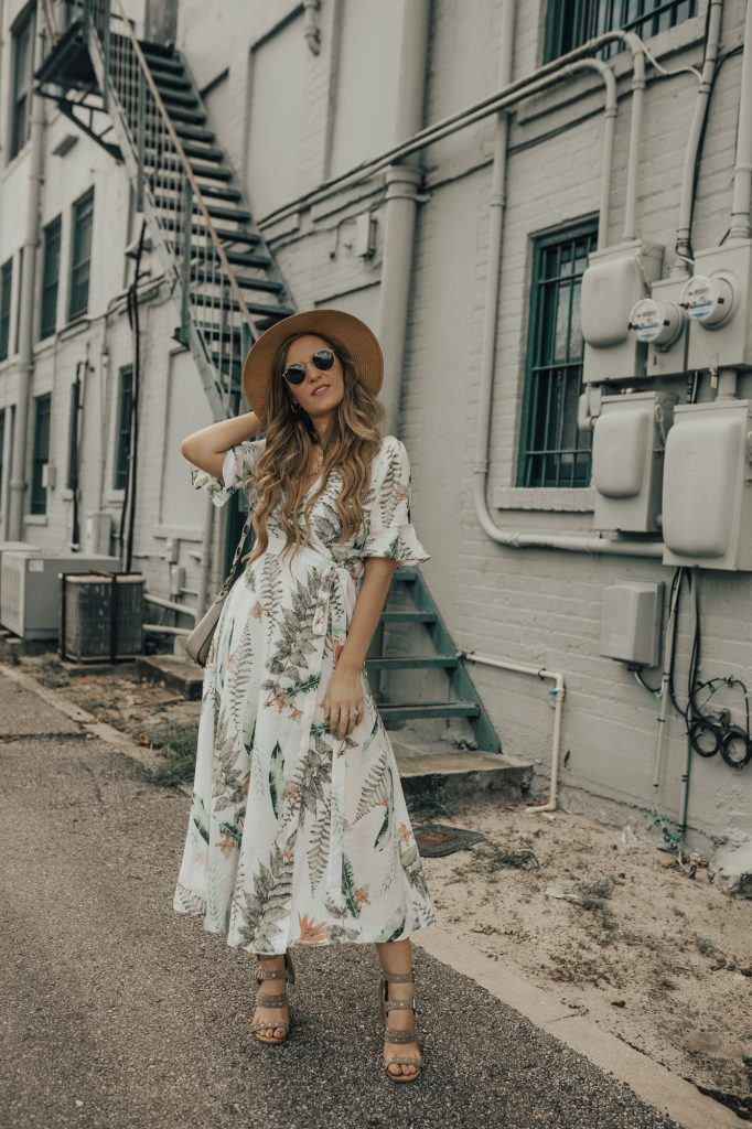 Shannon Jenkins of Upbeat Soles styles a cute vacation outfit with palm print midi dress, Dolce Vita block heel sandals, and straw hat