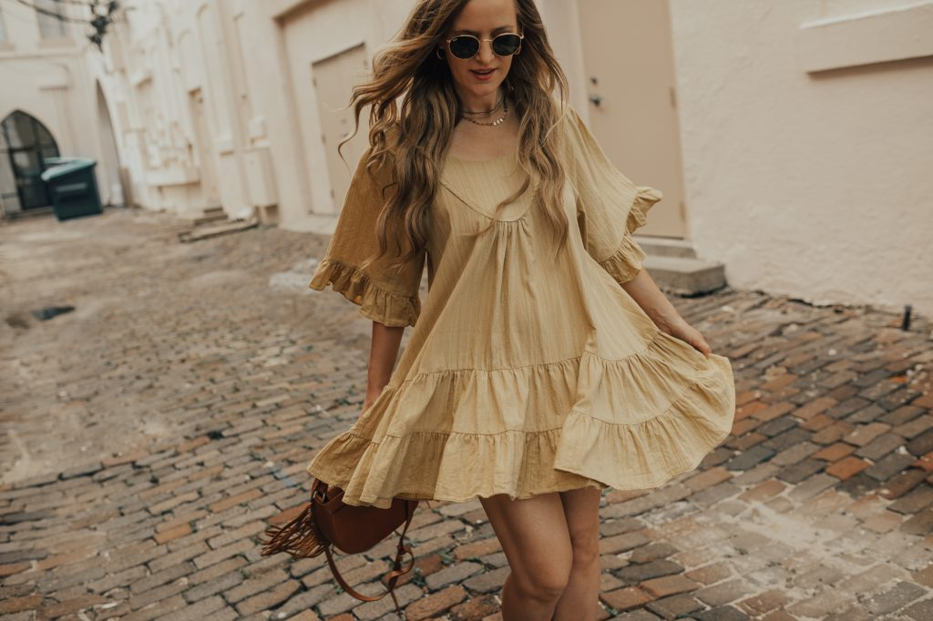 Shannon Jenkins of Upbeat Soles styles a summer boho outfit with mustard ruffle dress, lace up block heel sandals, and fringe leather bag