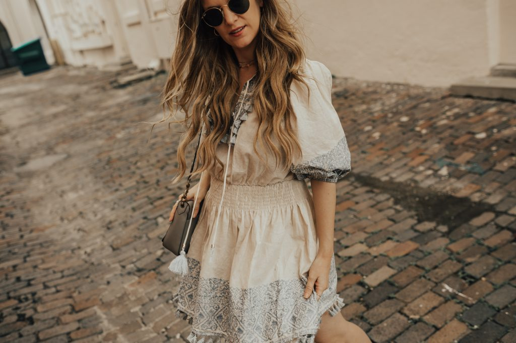 Shannon Jenkins of Upbeat Soles styles a boho fall transition outfit with tassel and embroidered dress, lace up Jeffrey Campbell booties, and round Ray Bans