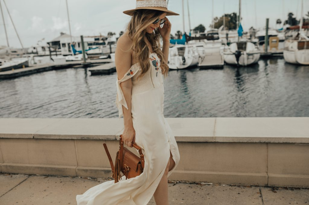 Shannon Jenkins of Upbeat Soles styles a cute summer vacation outfit with embroidered maxi dress, lace up sandals, and fringe crossbody bag