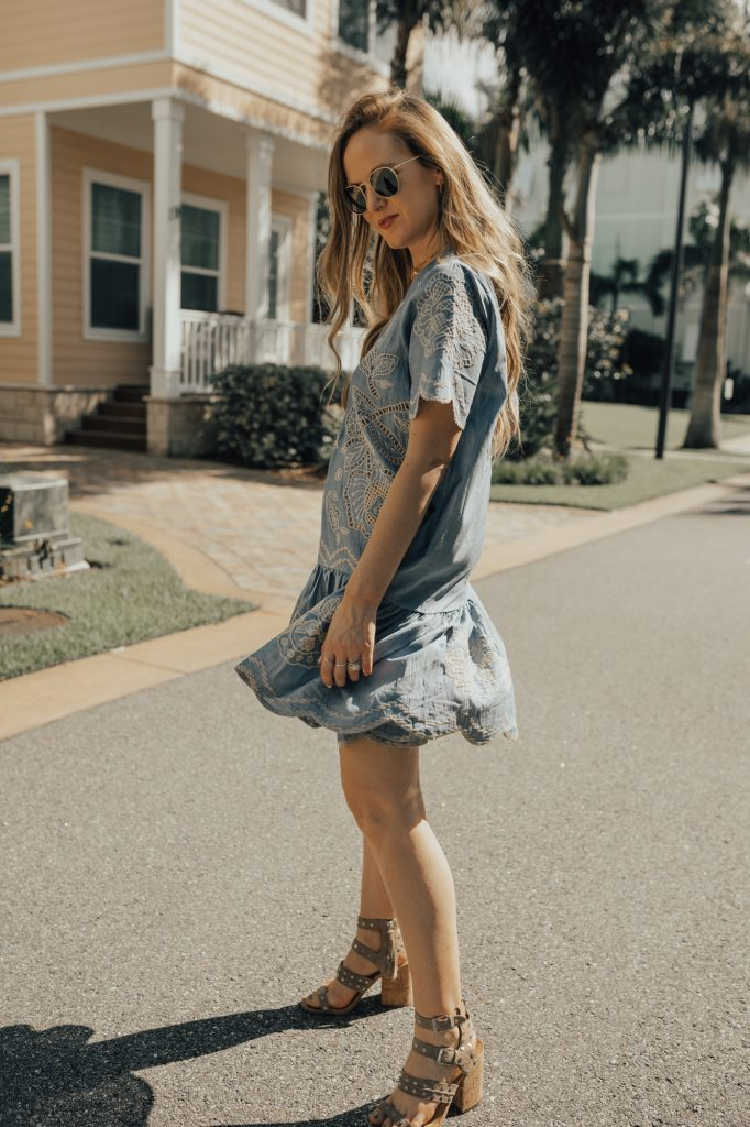 Shannon Jenkins of Upbeat Soles styles a day date outfit with Chicwish eyelet and ruffled dress, Dolce Vita block heels, and round Ray Ban sunglasses