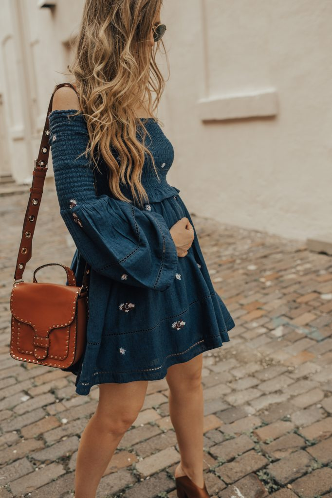 Shannon Jenkins of Upbeat Soles styles a boho fall transition outfit with Free People off the shoulder bell sleeve dress, and Kelsi Dagger metallic booties