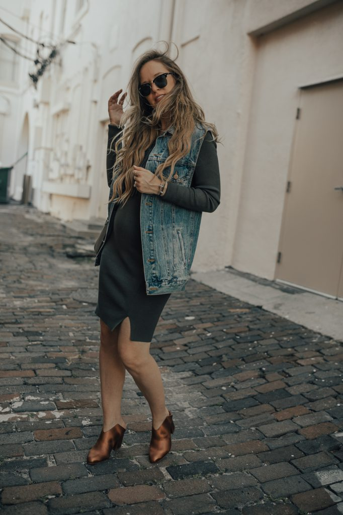 Shannon Jenkins of Upbeat Soles styles a cute fall maternity outfit with WAYF bodycon dress, boyfriend denim vest, and Kelsi Dagger metallic booties