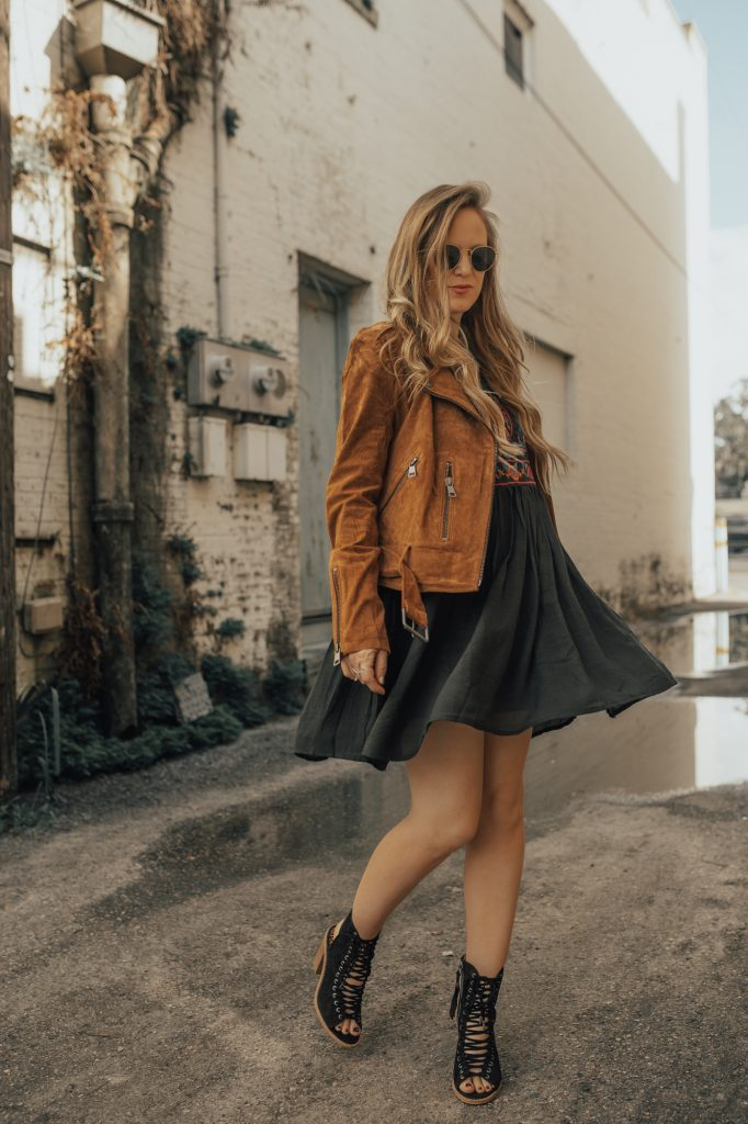 Shannon Jenkins of Upbeat Soles styles a boho fall transition outfit with embroidered bell sleeve dress, brown suede moto jacket, and black lace up booties