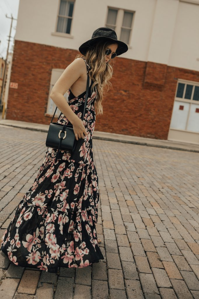 Shannon Jenkins of Upbeat Soles styles a fall transition outfit with Free People floral maxi dress, Free People gold sandals, and Sancia crossbody bag