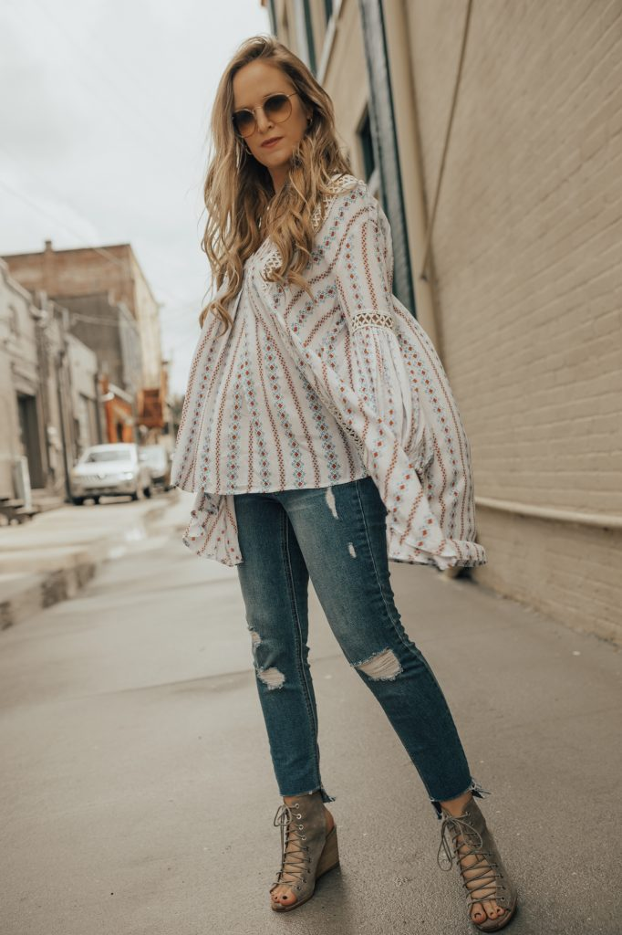 Shannon Jenkins of Upbeat Soles styles a boho maternity outfit with Chicwish flowy tunic, distressed jeans, lace up wedges, and round sunglasses