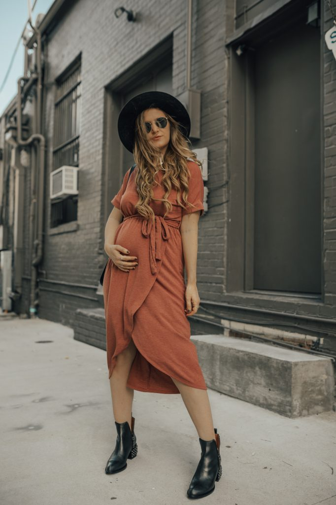 Shannon Jenkins of Upbeat Soles styles and edgy fall maternity outfit with sweater wrap dress, studded Jeffrey Cambell booties, and Sancia crossbody bag