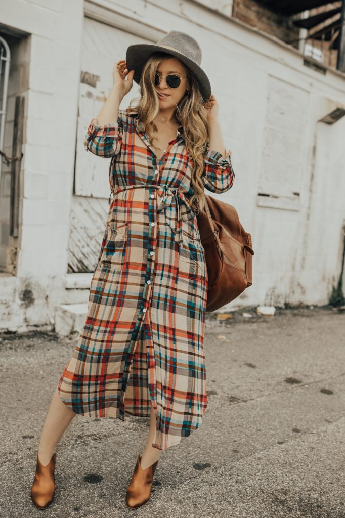 Shannon Jenkins of Upbeat Soles styles a fall maternity outfit with plaid maxi dress, metallic booties, Mahi Leather backpack, and round Ray Ban sunglasses