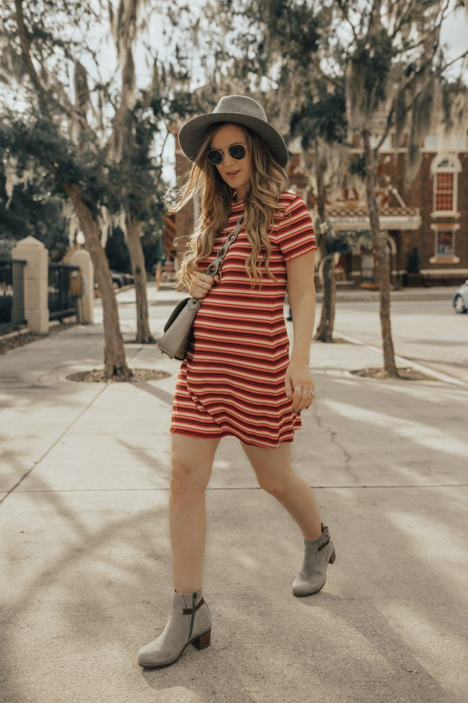 Shannon Jenkins of Upbeat Soles styles a maternity fall transition outfit with a striped Target dress, Dansko boots from Zappos, and round Ray Bans