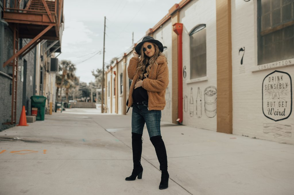 Shannon Jenkins of Upbeat Soles styles a winter maternity outfit with teddy jacket, black over the knee botts, and round Ray Ban sunglasses