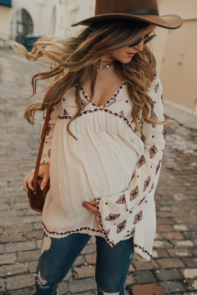 Shannon Jenkins of Upbeat Soles styles a boho maternity outfit with Free People embroidered tunic, distressed maternity jeans, and studded booties