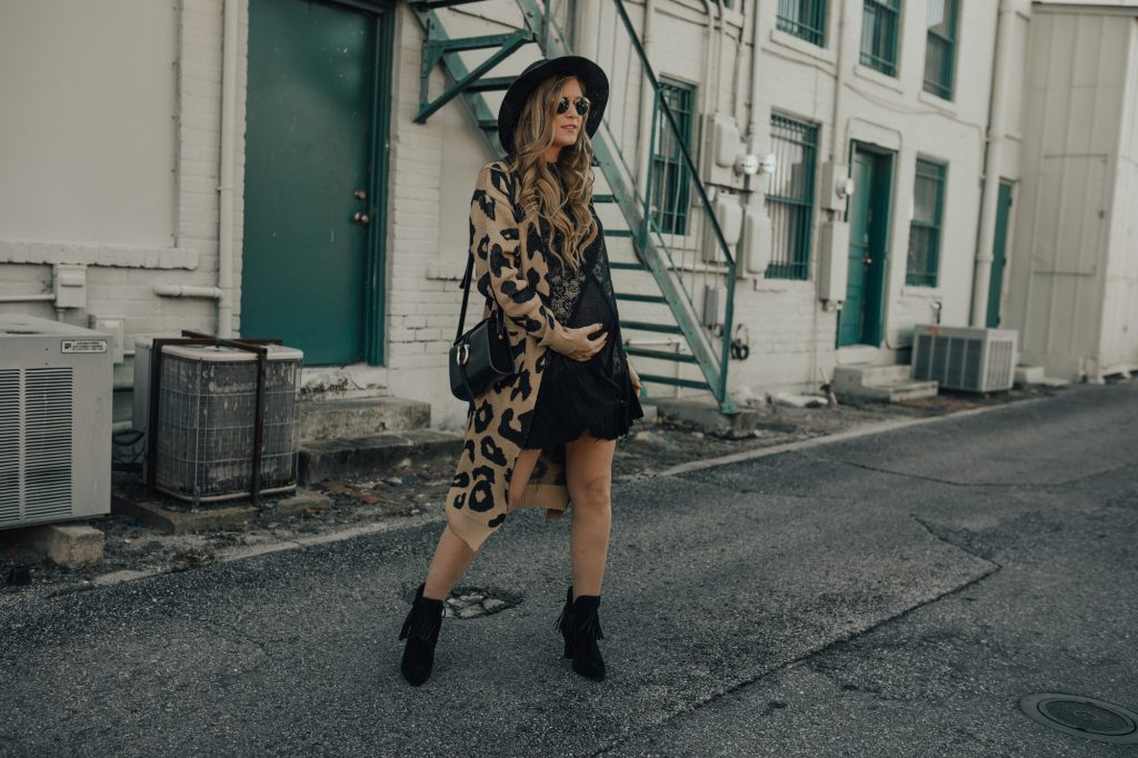 Shannon Jenkins of Upbeat Soles styles an edgy winter maternity outfit with Shein leopard duster, Free People lace swing dress, and black fringe booties