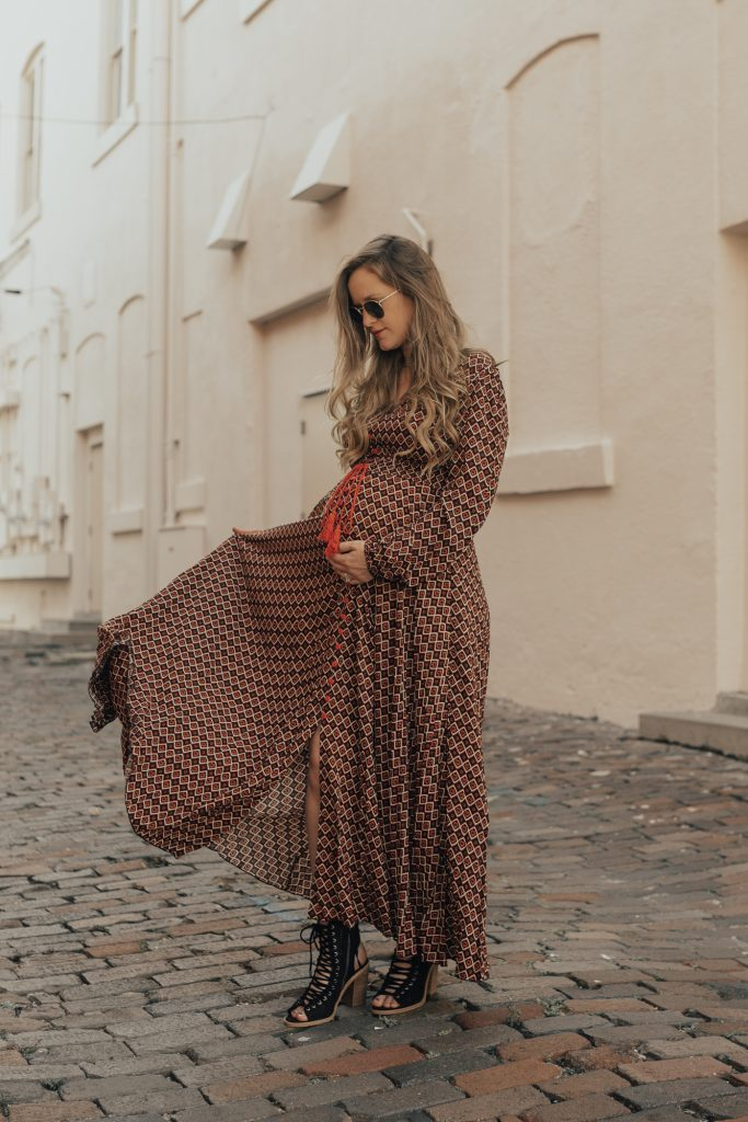 Shannon Jenkins of Upbeat Soles styles a boho maternity outfit with gemetric maxi dress, lace up booties, and round Ray Ban sunglasses
