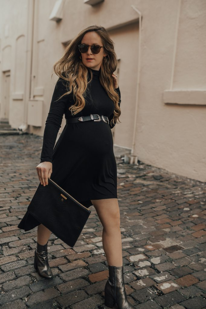 Shannon Jenkins of Upbeat Soles styles an edgy New Years Eve maternity outfit with high low turtleneck dress, double buckle belt, and metallic booties