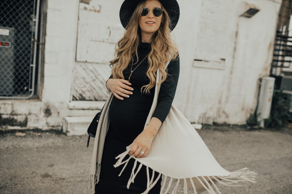Shannon Jenkins of Upbeat Soles styles a date night maternity outfit with Isabella Oliver black dress, fringe cardigan, and black ankle booties