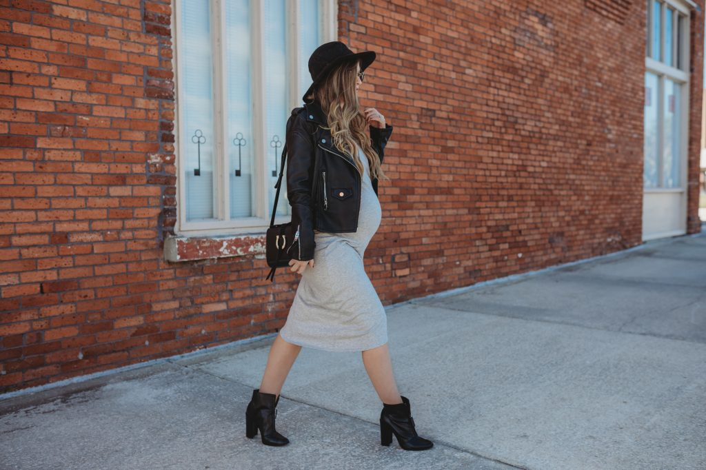 Shannon Jenkins of Upbeat Soles styles an edgy maternity outfit with gray wrap dress, leather moto jacket, black zip up booties, and Icon Ray Bans
