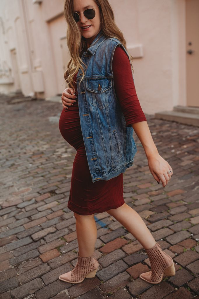 Shannon Jenkins of Upbeat Soles styles a stylish maternity outfit with Isabella Oliver burgundy dress, oversized denim vest, and Jeffrey Campbell woven boot