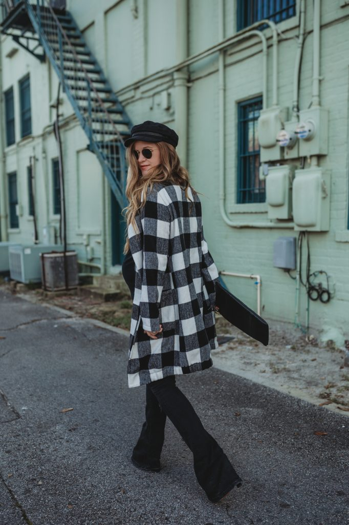 Shannon Jenkins of Upbeat Soles styles a winter maternity outfit with buffalo plaid cardigan, black flared jeans, and newsboy hat