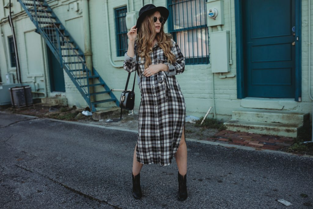 Shannon Jenkins of Upbeat Soles styles a spring transition maternity outfit with Sanctuary plaid shirt dress, zip up black booties, and black hat