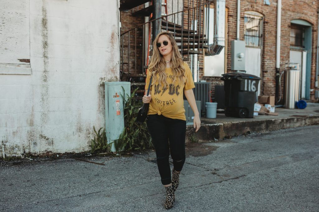 Shannon Jenkins of Upbeat Soles styles an edgy maternity outfit with ACDC band tee, ripped maternity jeans, and pony hair leopard booties