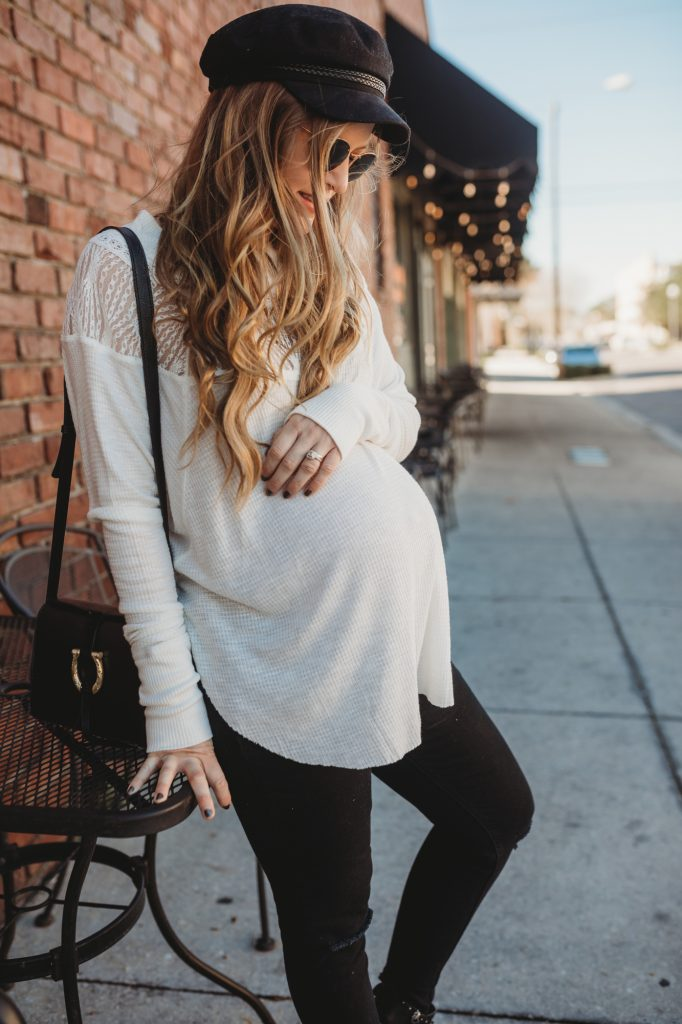 Shannon Jenkins of Upbeat Soles styles and edgy stylish maternity outfit with Free People henley, black distressed maternity jeans, and studded buckle boots
