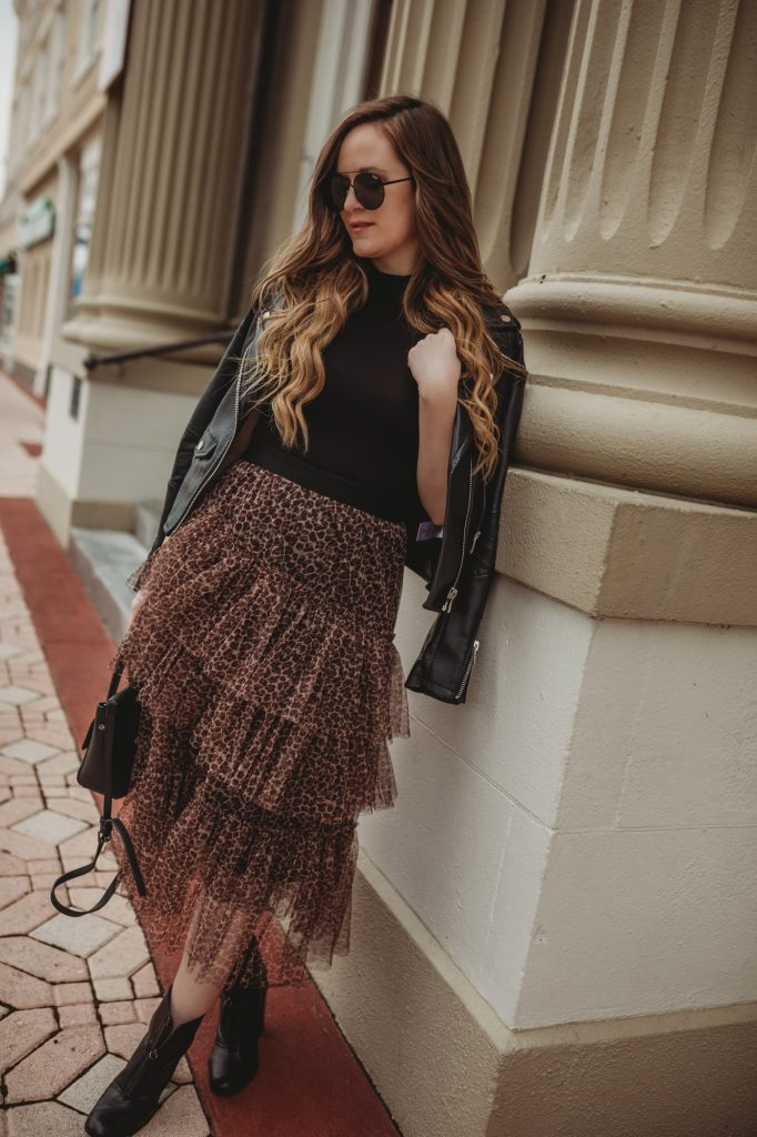 Shannon Jenkins of Upbeat Soles styles an edgy girls night out outfit with mock neck bodysuit, Chicwish leopard tulle skirt, and black zip up booties