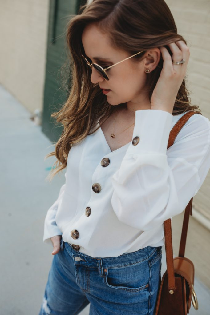 Shannon Jenkins styles a cute weekend outfit with button down white top, high waisted mom jeans, caged booties, and garnet necklace and earrings
