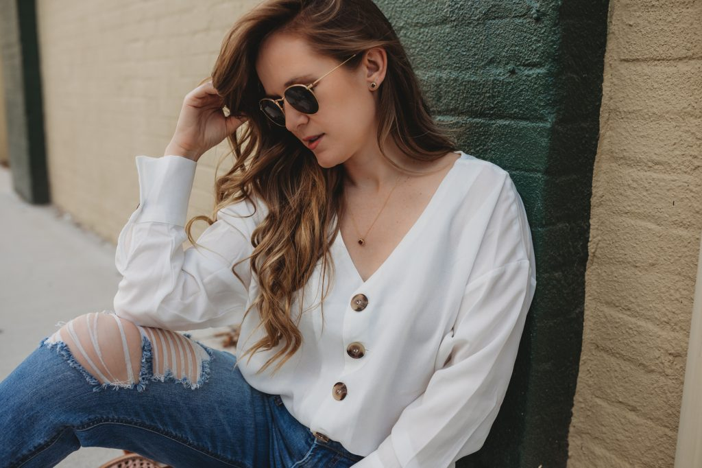 Shannon Jenkins styles a cute weekend outfit with button down white top, high waisted mom jeans, caged booties, and granet necklace and earrings