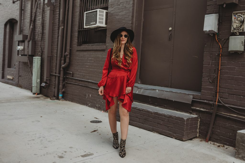 Shannon Jenkins of Upbeat Soles styles a spring boho outfit with a red wrap dress, animal print booties, black hat, and round Ray Ban sunglasses