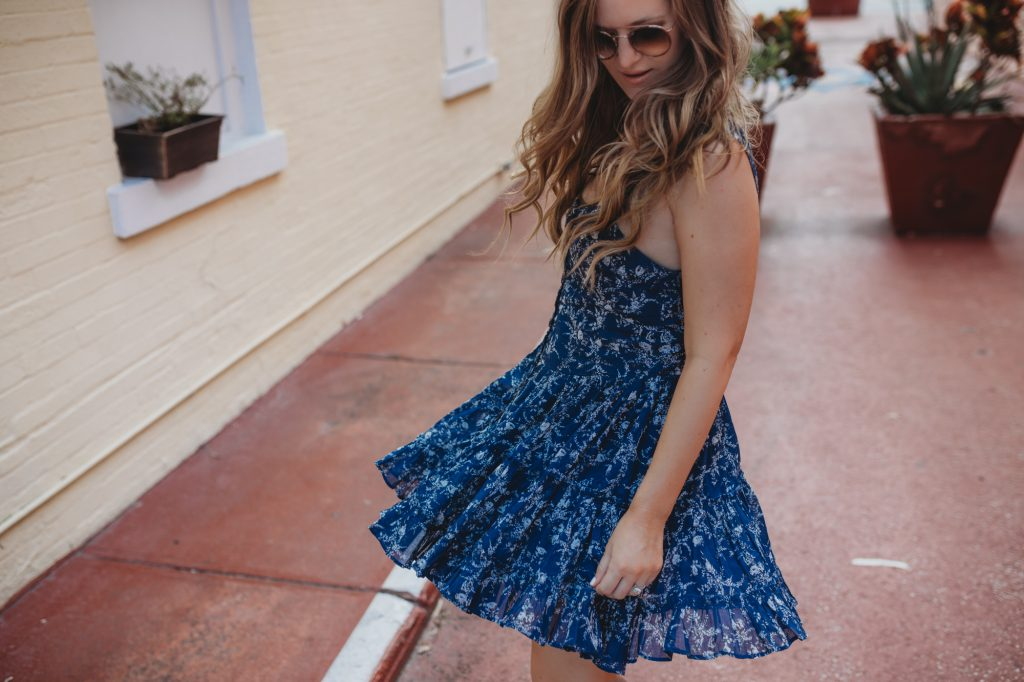 Shannon Jenkins of Upbeat Soles styles a flirty spring outfit with Free People floral dress, Jeffrey Campbell lace up wedges, and round Ray Ban sunglasses