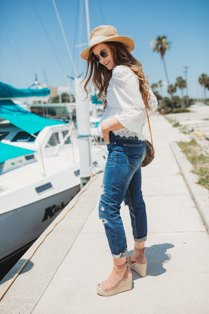 Shannon Jenkins of Upbeat Soles styles a cute summer outfit with white peplum top, high waisted mom jeans, Dolce Vita espadrille wedges, and round rattan bag