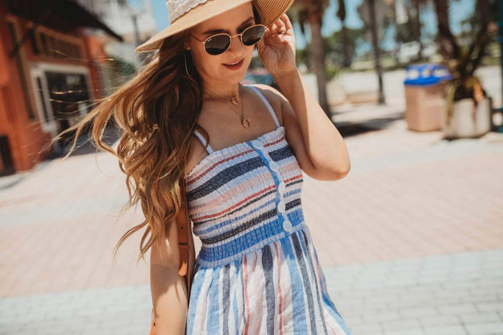 Shannon Jenkins of Upbeat Soles styles a summer vacation outfit with a striped linen midi dress, Soludos espadrille sandals, and Ray Ban Icons