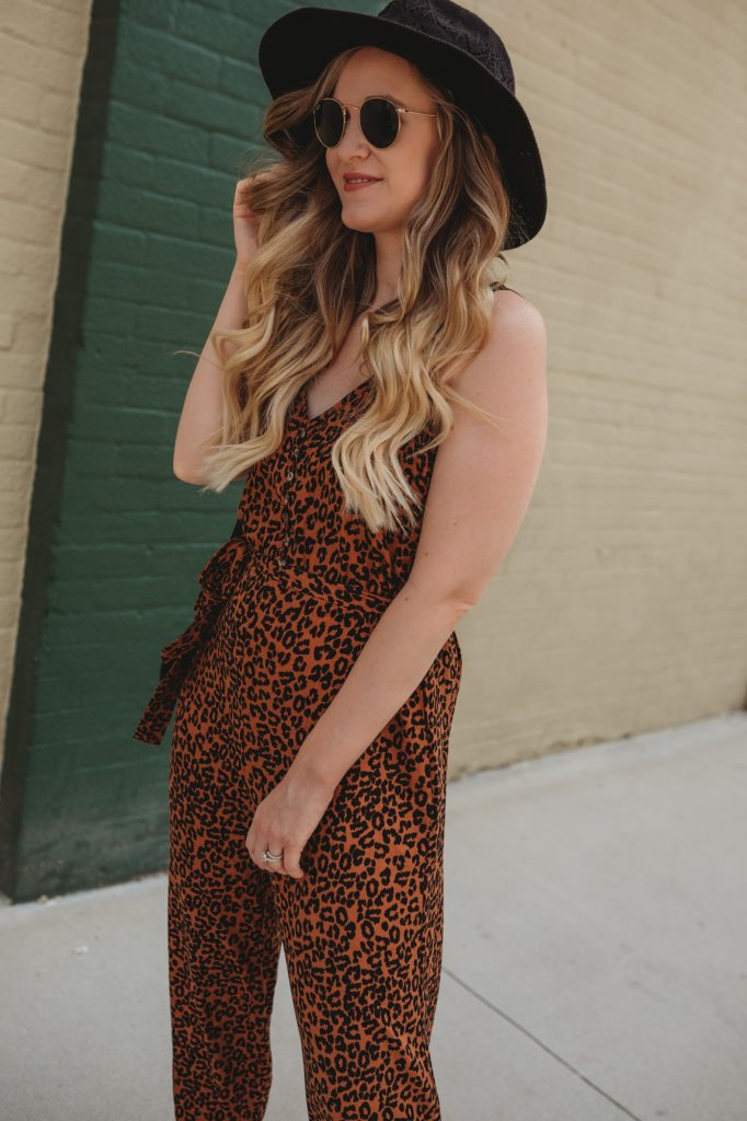 Shannon Jenkins of Upbeat Soles styles a cute leopard jumpsuit from American Eagle, ankle cowboy boots, and Ray Ban Icon sunglasses