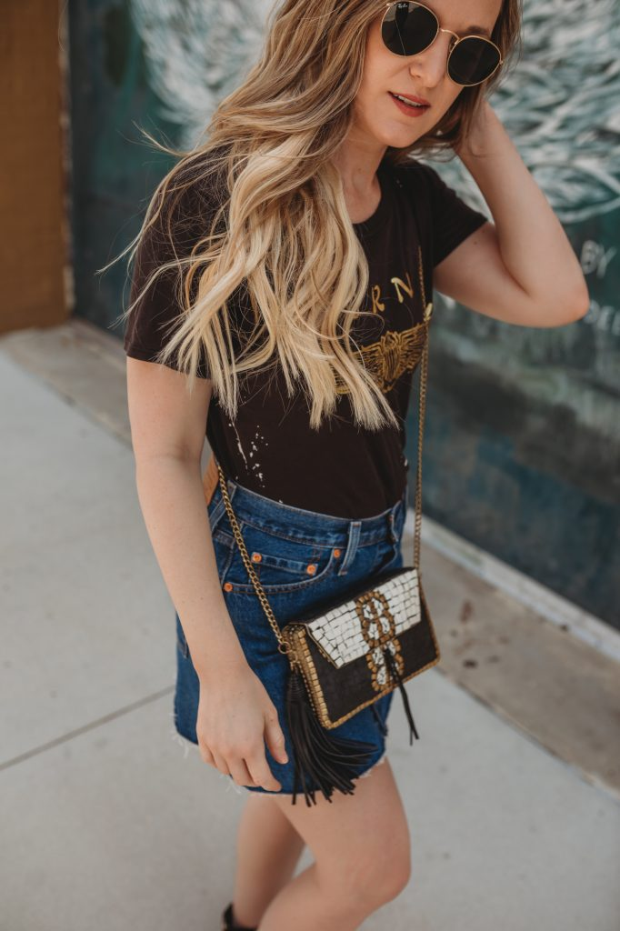 Shannon Jenkins of Upbeat Soles styles a cute rock concert outfit with Chaser band tee, Levi's button down denim skirt, and animal print booties