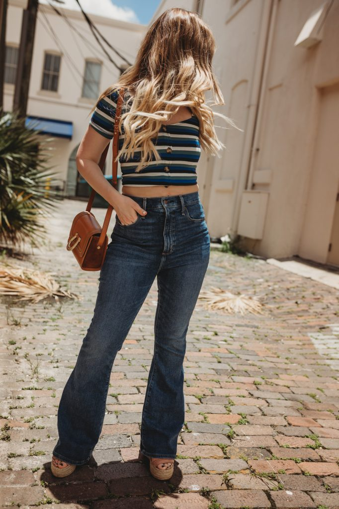 Shannon Jenkins of Upbeat Soles shoes how to style flared jeans with a striped crop top from Abercrombie and Dolce Vita wedges