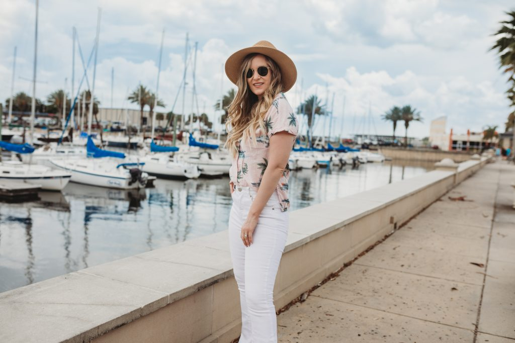 Shannon Jenkins of Upbeat Soles styles a cute summer outfit with tropical button down shirt, white high waisted flared jeans, straw hat, and round Ray Bans
