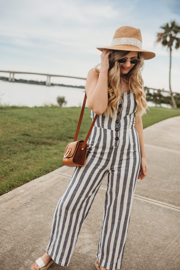 Shannon Jenkins of Upbeat Soles styes a cute summer vacation outfit with JOA striped jumpsuit, metallic espadrille sandals, and straw panama hat