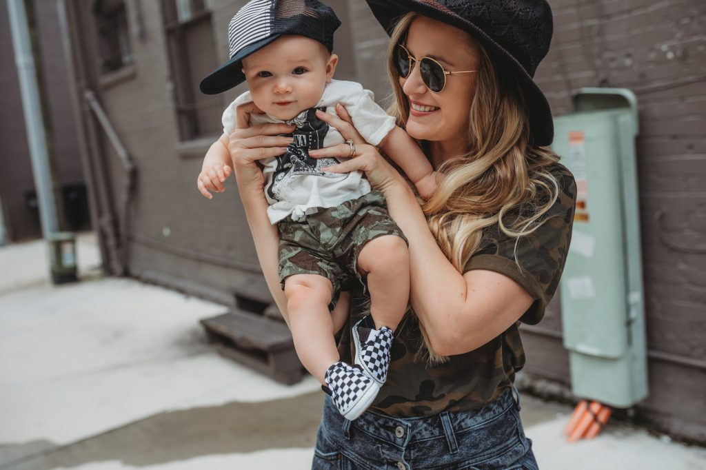 Shannon Jenkins of Upbeat Soles styles a cute boy mommy and me outfit with baby band tee, camo shorts, baby Vans, and George Hat