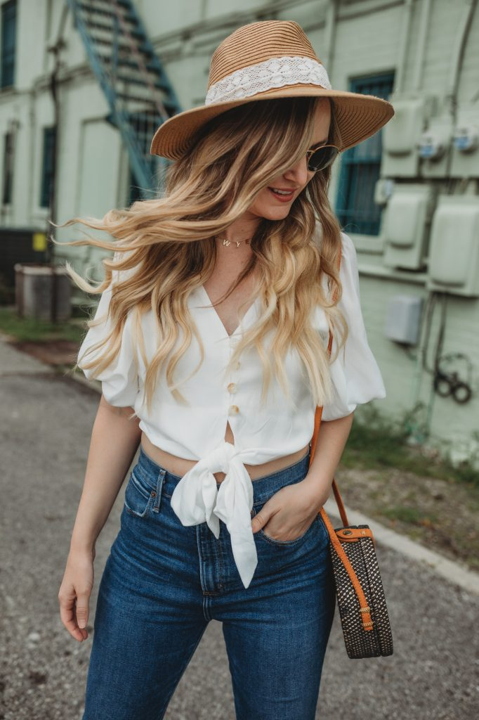 Shannon Jenkins of Upbeat Soles styles a flared jeans outfit with Chicwish bow crop top, Abercrombie flared jeans and round rattan bag