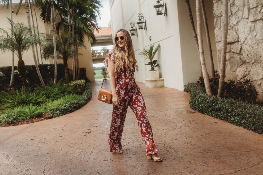 Shannon Jenkins of Upbeat Soles styles a fall transition jumpsuit perfect for date night that is a floral and burgundy jumpsuit paired with Sancia bag
