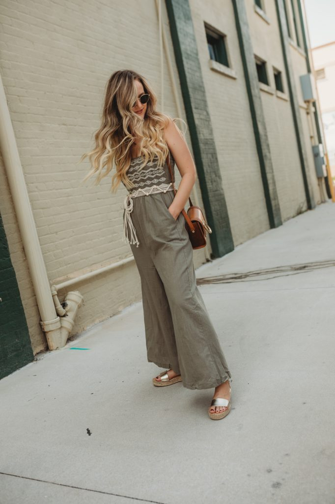 Shannon Jenkins of Upbeat Soles styles a casual summer outfit with olive jumpsuit, metallic espadrille sandals, and round Ray Ban sunglasses