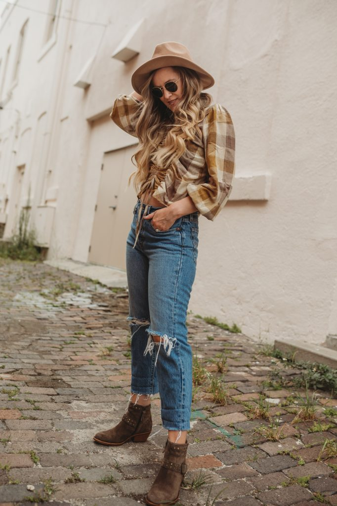 Shannon Jenkins of Upbeat Soles styles a fall transition outfit with plaid crop top. Levi's high waisted jeans, and Sofft booties